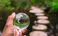 a hand holds a crystal reflecting a pond and millstones